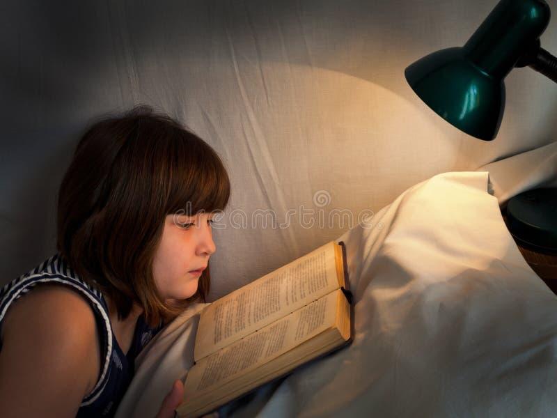 Tonårig flickaläsebok på säng på natten royaltyfri bild