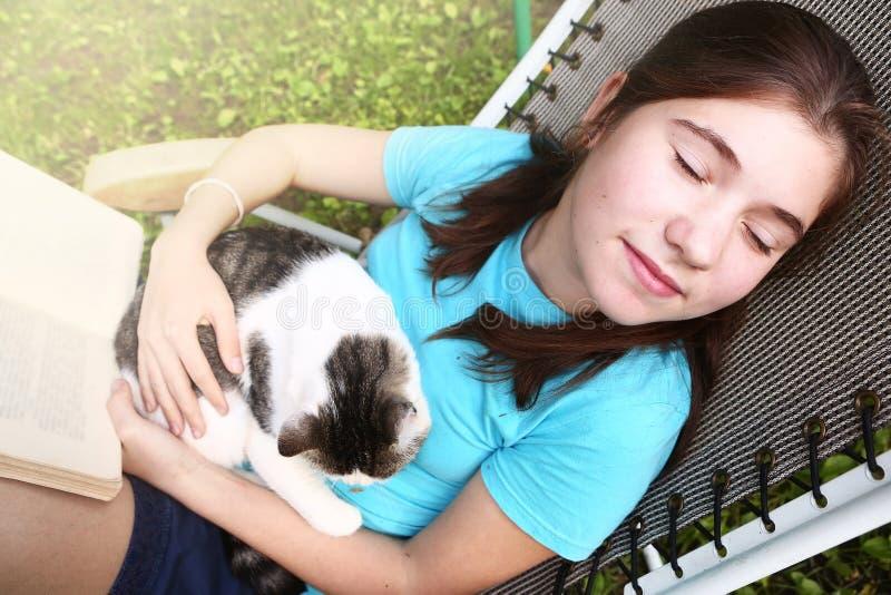 Tonårig flickasömn i chaisevardagsrum med katten royaltyfria bilder