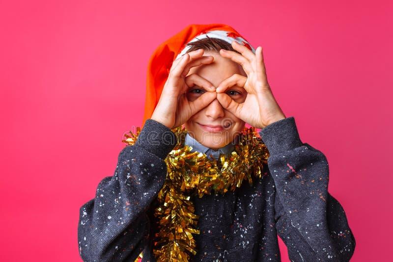 Tonårig grabb i hatt för jultomten` s och med glitter på hans hals, reko si för shower arkivbilder