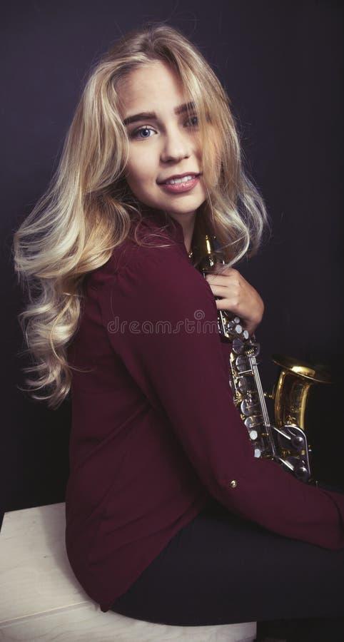Tonårig hållande saxofon royaltyfria foton