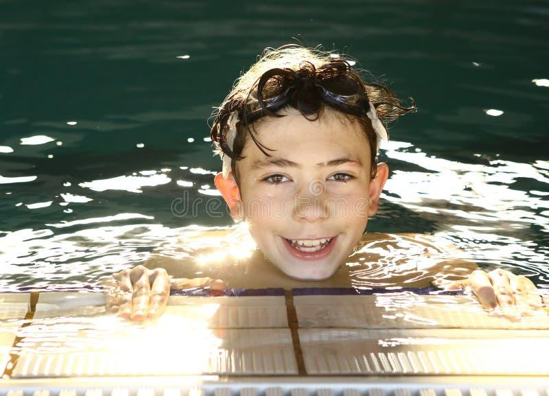 Tonårig lycklig pojke i simbassängen royaltyfri foto