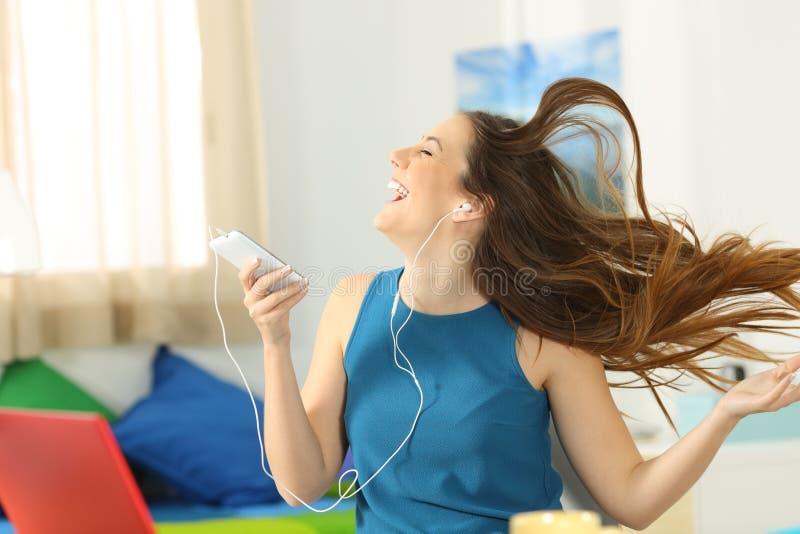 Tonårig lyssnande musik och dansa i hennes rum arkivbild