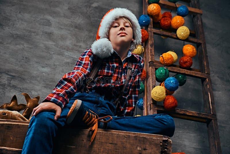 Tonårig pojke i jultomten hatt som bär en rutig skjorta med hängslen som sitter på en palett bredvid en trädekorerad stege arkivfoton