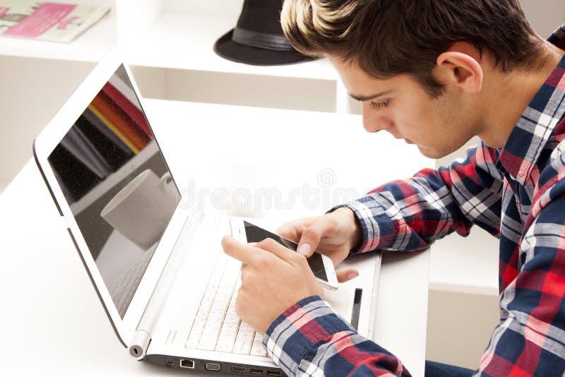 Tonårig pojke med bärbara datorn och mobiltelefonen arkivbild
