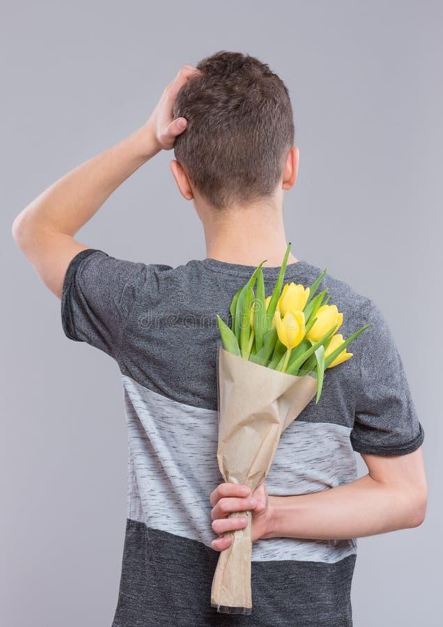 Tonårig pojke med blommor royaltyfria bilder