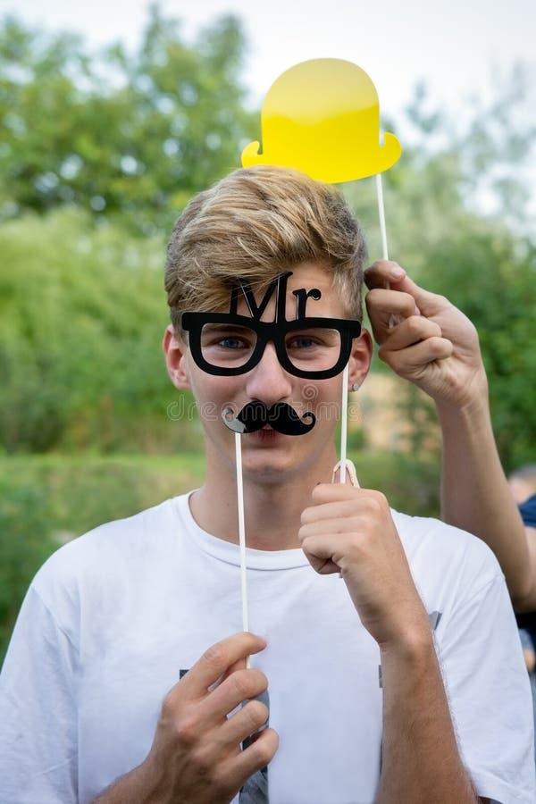 Tonårig pojke med mustaschen, exponeringsglas och hattmunterhet på partiet arkivfoton