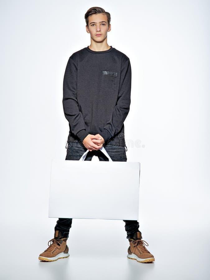 Tonårig pojke med shoppingpåsar på studion arkivfoto