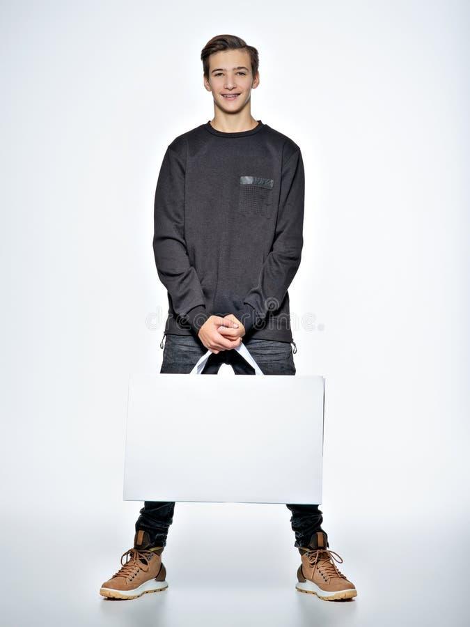 Tonårig pojke med shoppingpåsar på studion royaltyfri bild