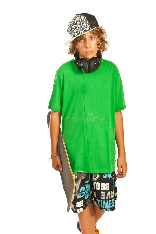 Tonårig pojke med skateboarden arkivbild