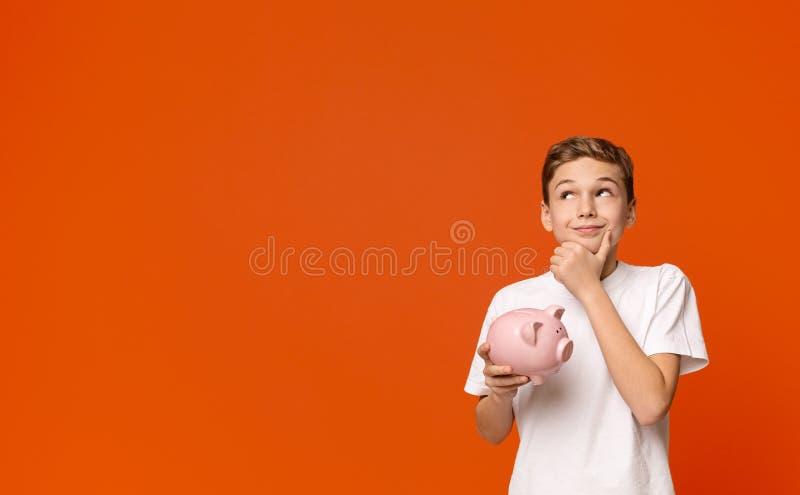Tonårig pojke med spargrisen som drömmer om någon saker som han kan köpa royaltyfri bild