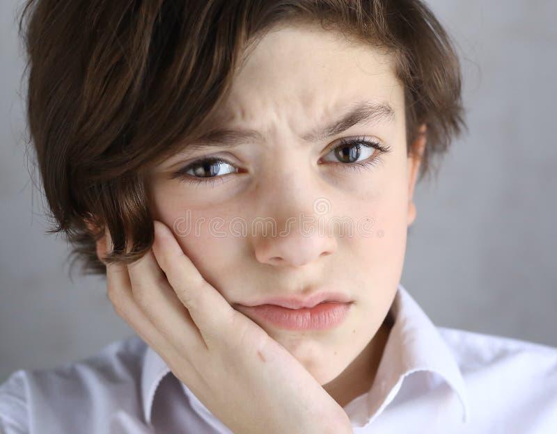 Tonårig pojke med tandvärk som rymmer hans kind royaltyfria bilder
