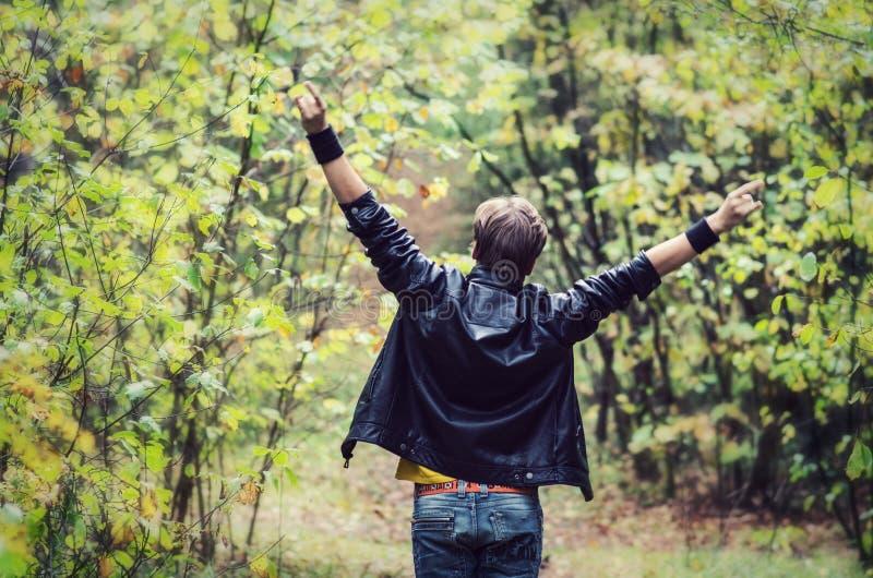 Tonårig pojke med utsträckta armar royaltyfria bilder