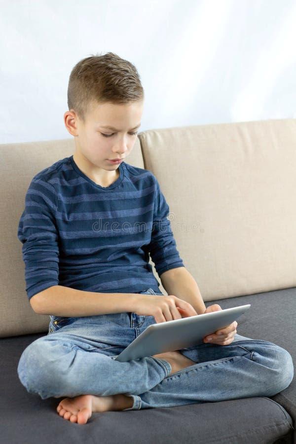 Tonårig pojke som använder minnestavlan Barnpojke som spelar leken eller hemma kontrollerar socialt massmedia på minnestavlan und arkivbilder