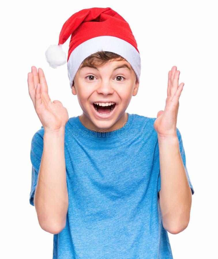 Tonårig pojke som bär den Santa Claus hatten arkivfoto