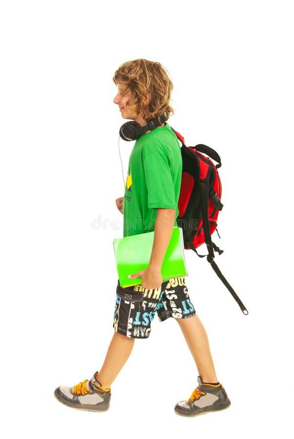 Tonårig pojke som går till skolan fotografering för bildbyråer