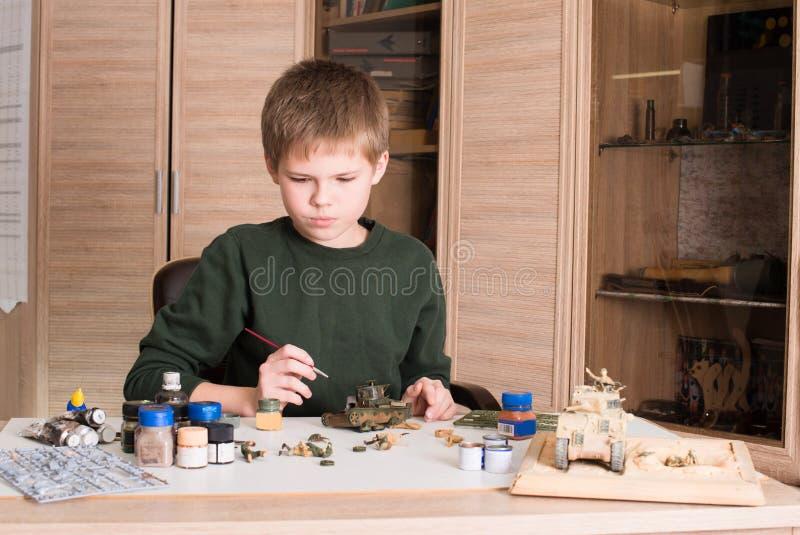 Tonårig pojke som monterar och målar den plast- modellbehållaren på arbetsplatsen royaltyfria foton