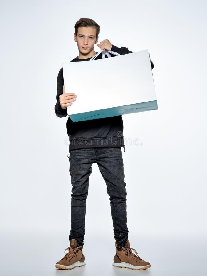Tonårig pojke som rymmer shoppingpåsar på studion royaltyfri fotografi