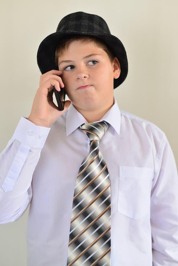 Tonårig pojke som talar på mobiltelefonen på ljus bakgrund arkivfoto