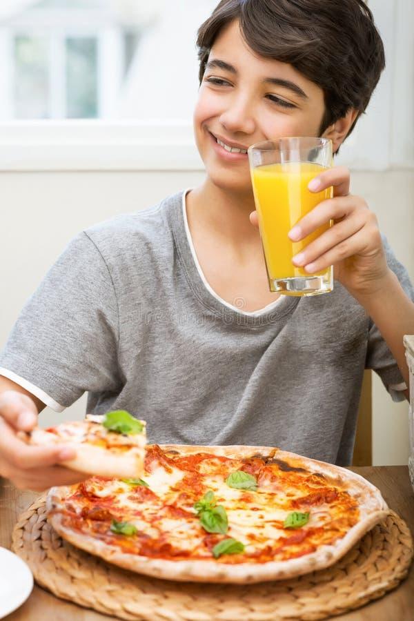 Tonårig pojke som tycker om pizza och fruktsaft royaltyfri fotografi