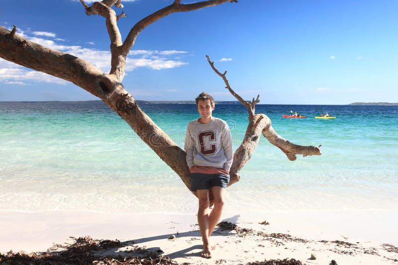 Tonårig pojke som tycker om tropisk ferie för strandfritidsemester arkivbild