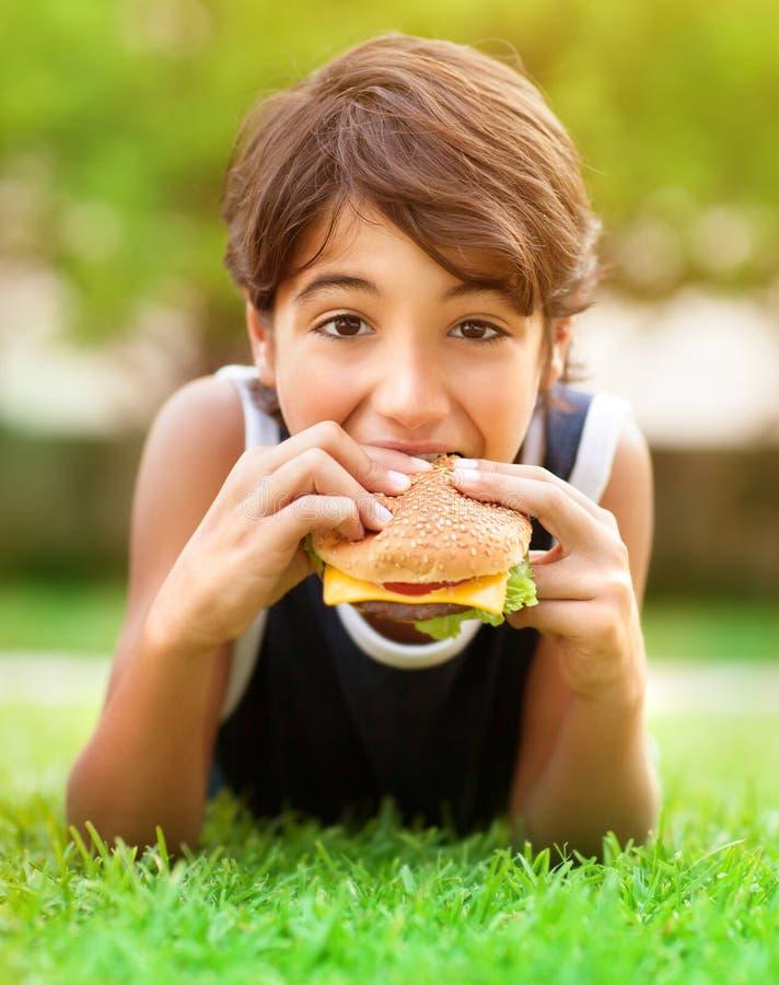 Tonårig pojke som utomhus äter hamburgaren arkivbild