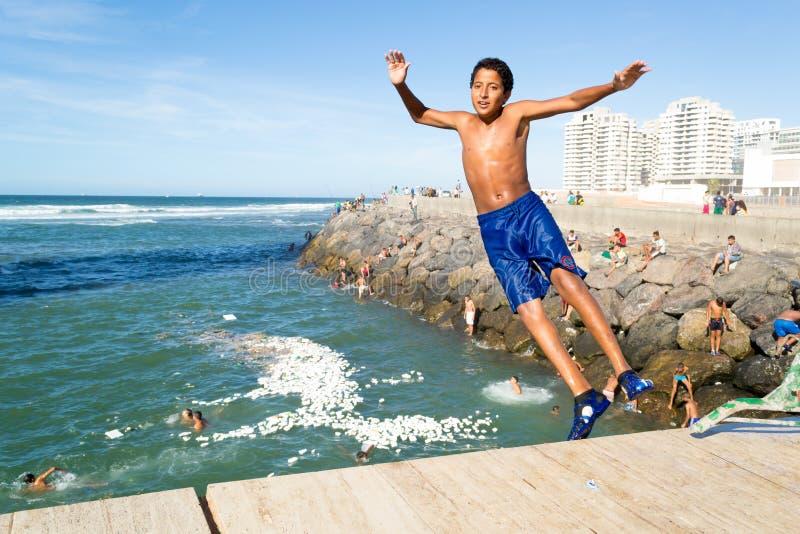Tonårig pojkebanhoppning i havet i Casablanca Marocko #2 arkivfoton