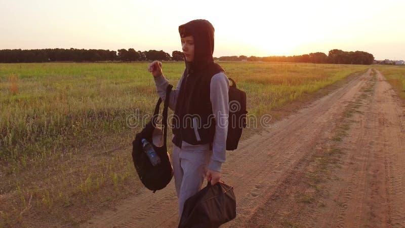 Tonårig resande för pojke Tonårs- slampa för pojke som promenerar vägen i en huv med ryggsäckar en ledsen handelsresande royaltyfri bild
