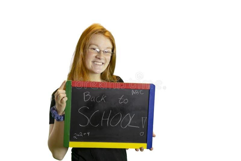Tonårig rymmande baksida till skolasvart tavla fotografering för bildbyråer
