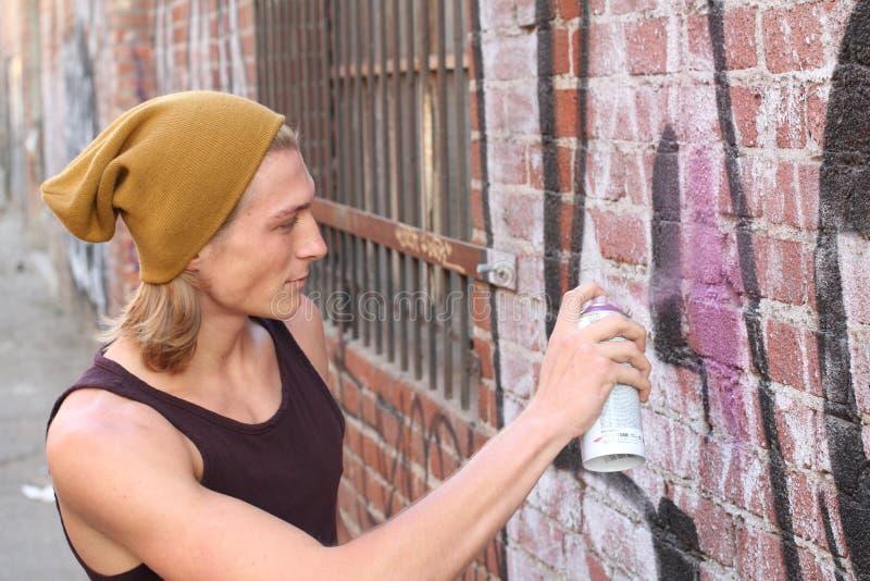 Tonårig stilig pojke och grafitti royaltyfri foto