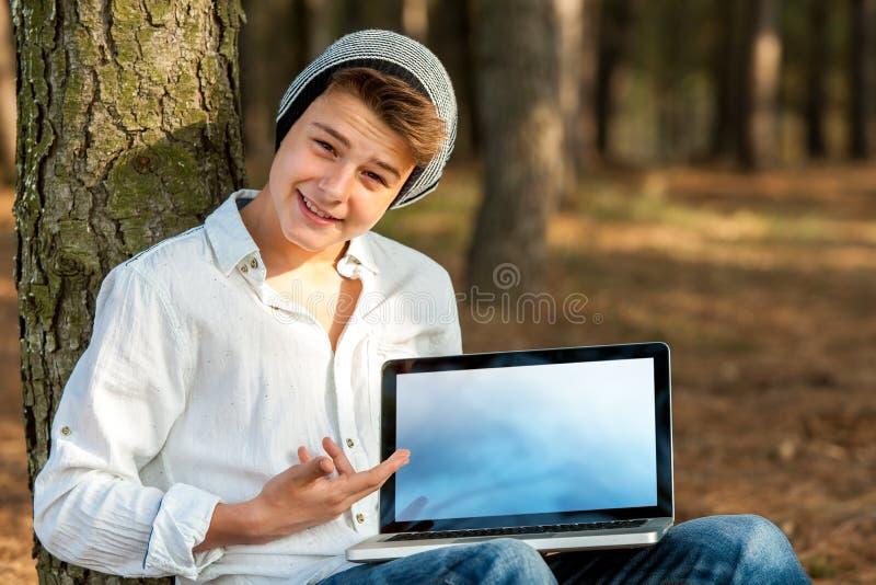 Tonårig student som pekar på den tomma bärbar datorskärmen. royaltyfri foto
