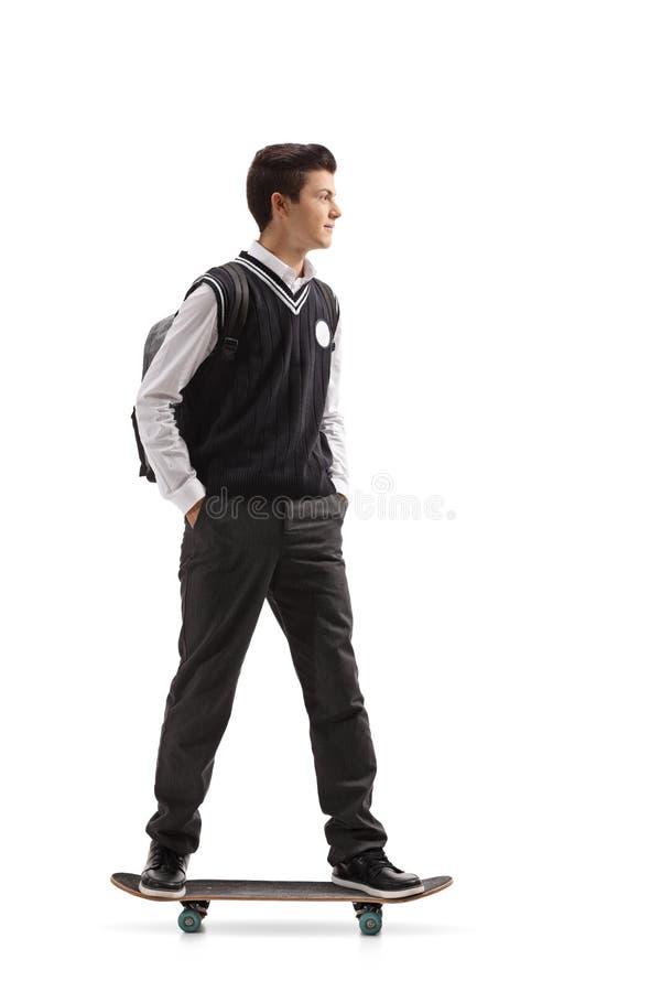 Tonårig student som rider en skateboard royaltyfria foton