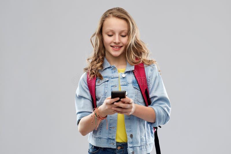 Tonårig studentflicka med skolapåsen och smartphonen arkivbild