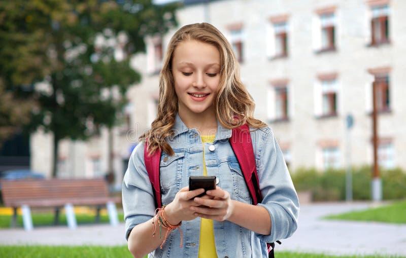 Tonårig studentflicka med skolapåsen och smartphonen royaltyfri fotografi