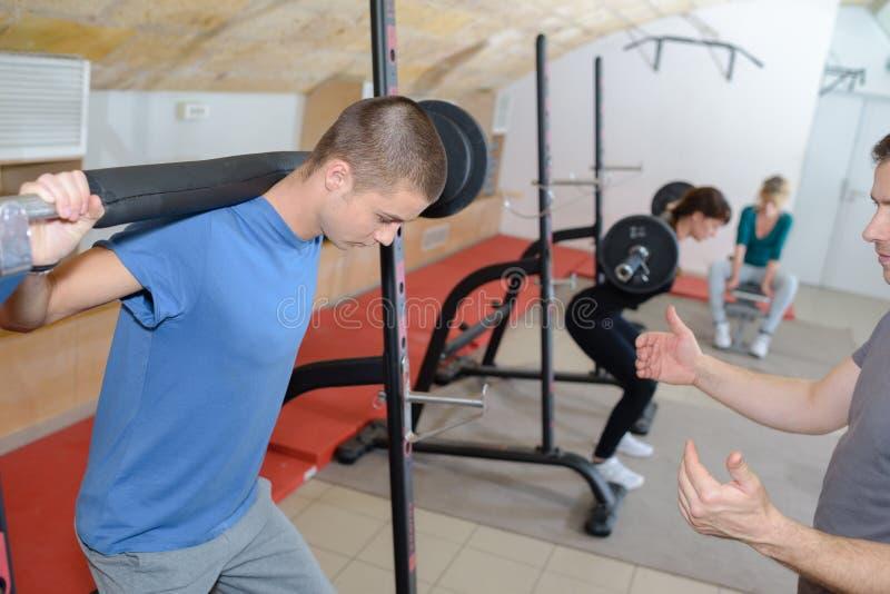 Tonårig utbildning med vikter på idrottshallklubban med lagledaren arkivfoton