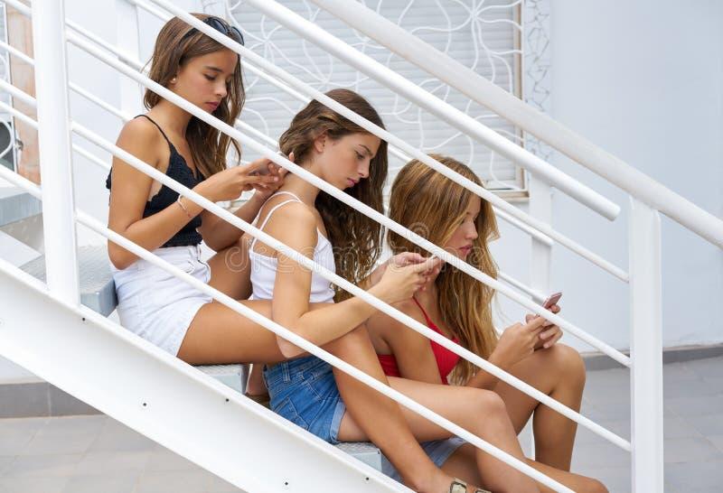 Tonåriga bästa vänflickor i rad med smartphonen arkivfoton
