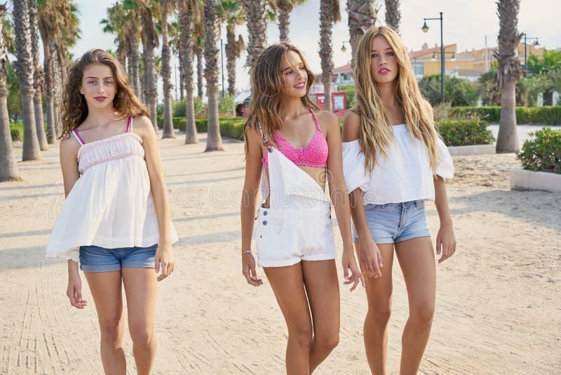 Tonåriga bästa vänflickor som går i palmträd fotografering för bildbyråer