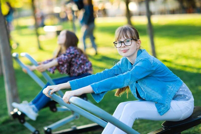 Tonåriga flickor övar knuffar utomhus- muskler - arkivbilder