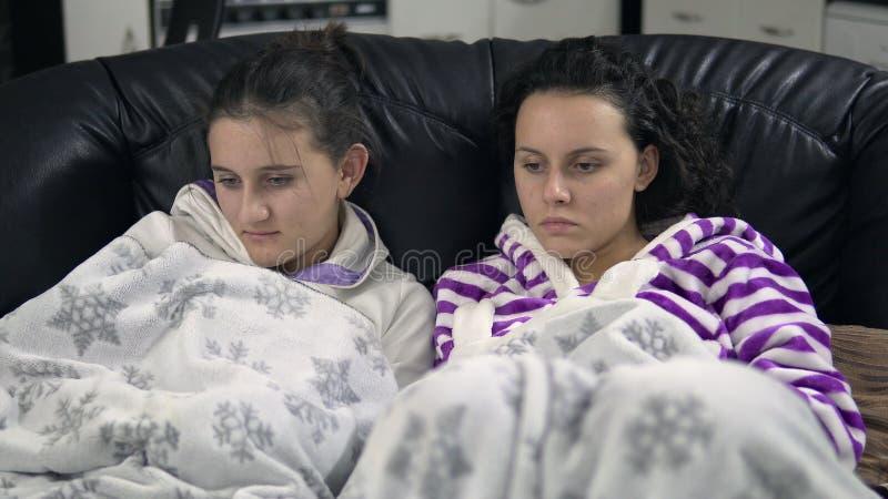 Tonåriga flickor i pijamas som sitter på soffan med filt- och klockaTV arkivbild