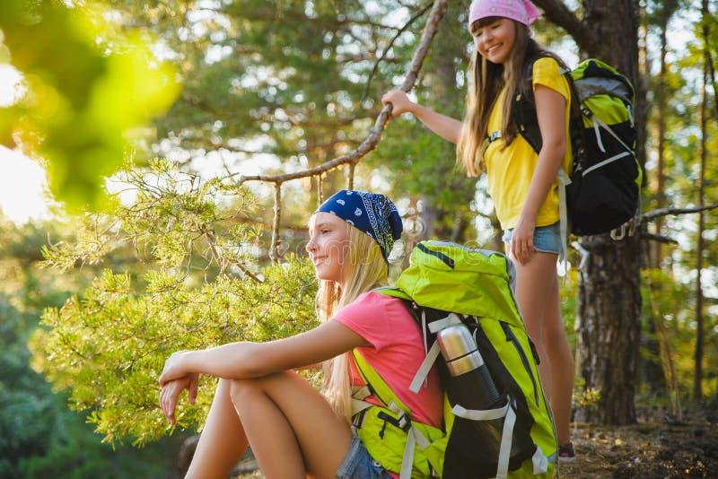 Tonåriga flickor med ryggsäcken som vilar i skoglopp och turismbegrepp fotografering för bildbyråer