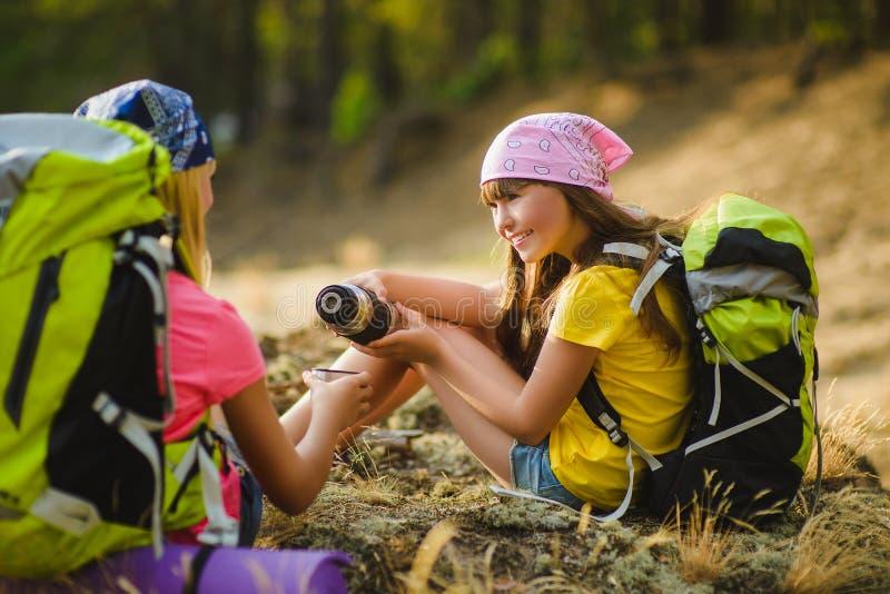 Tonåriga flickor med ryggsäcken som vilar, och drinkte Lopp- och turismbegrepp arkivfoton