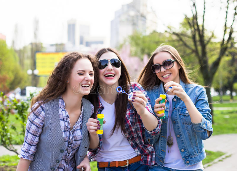 Tonåriga flickor som blåser såpbubblor Unga lyckliga tonåringar som har gyckel i sommar, parkerar royaltyfria bilder