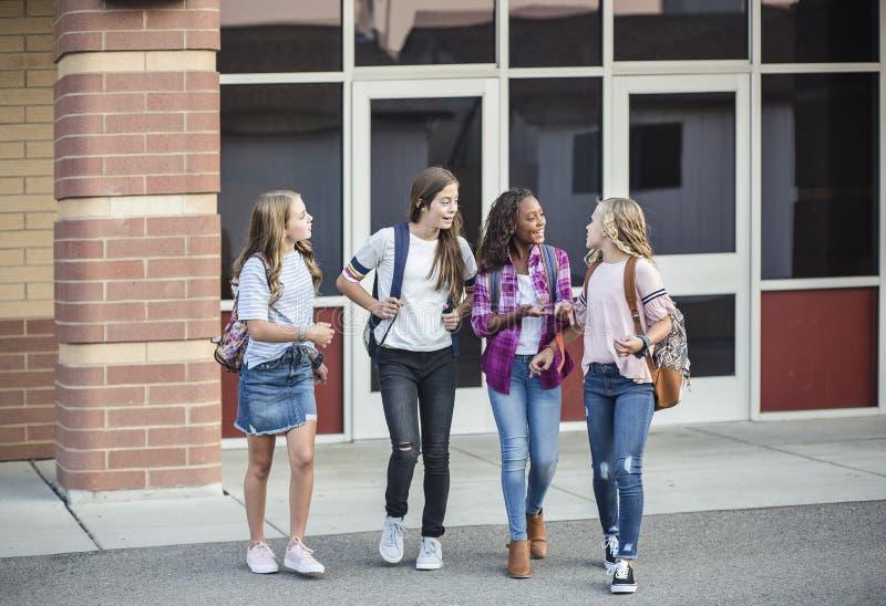Tonåriga flickor som lämnar skolan samtal och gå tillsammans royaltyfri bild