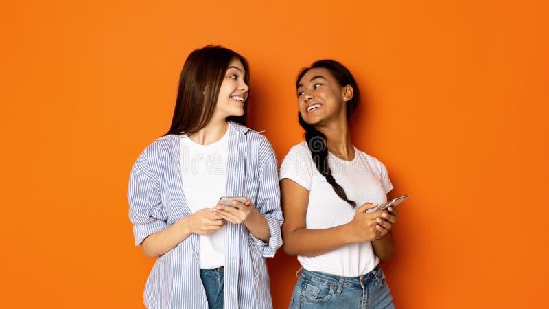Tonåriga flickor som ser de och använder mobiltelefoner fotografering för bildbyråer