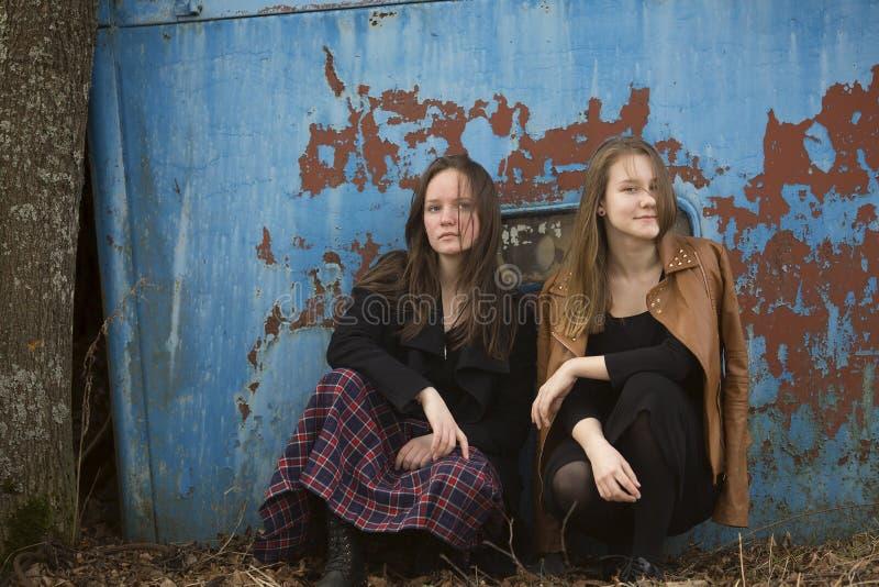 Tonåriga flickor som sitter på en bakgrund av den gamla järnväggen Natur royaltyfria bilder