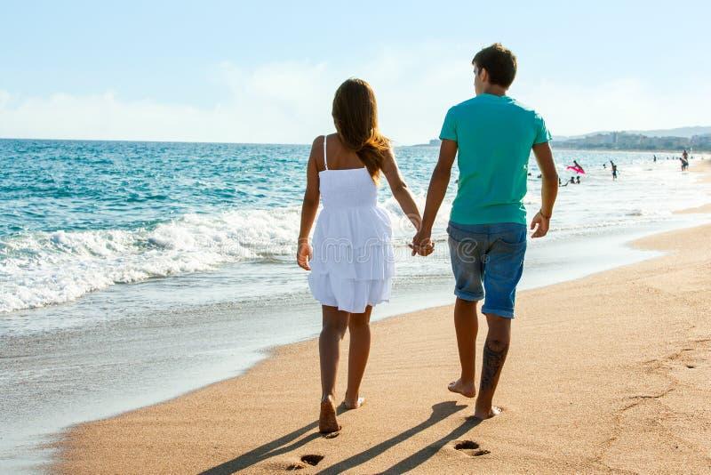 Tonåriga par som bort går på stranden. royaltyfria bilder