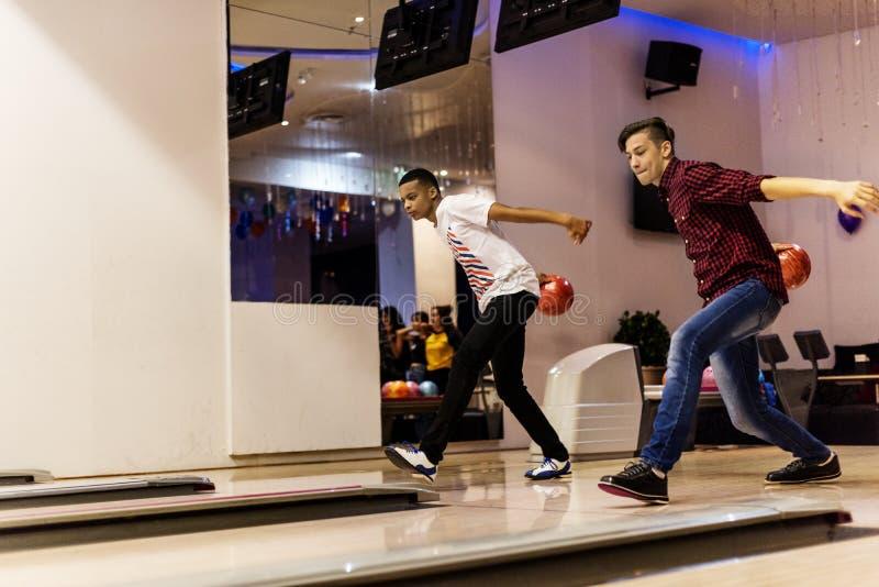 Tonåriga pojkar som tillsammans på en gång bowlar arkivfoton