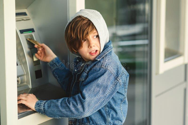 Tonåriga pojken för problem tar den pre i huv, pengar den kontanta utmataren för främmande kort Pojken tar kassa på ATM-maskinen  royaltyfria bilder