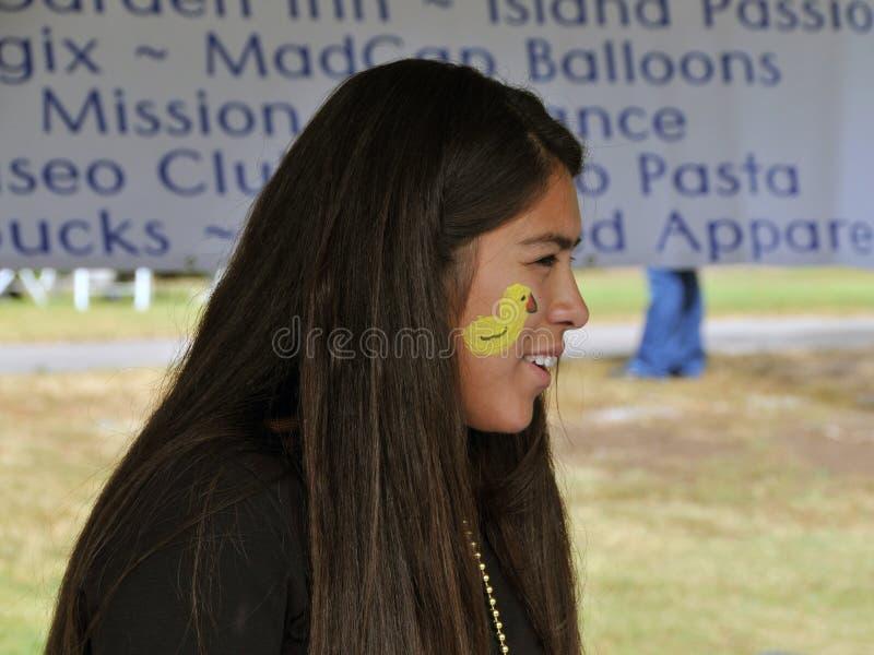 Tonåriga sportar för en flickavolontär en rubber ducky framsidamålning under den rubber ducky festivalen royaltyfri foto