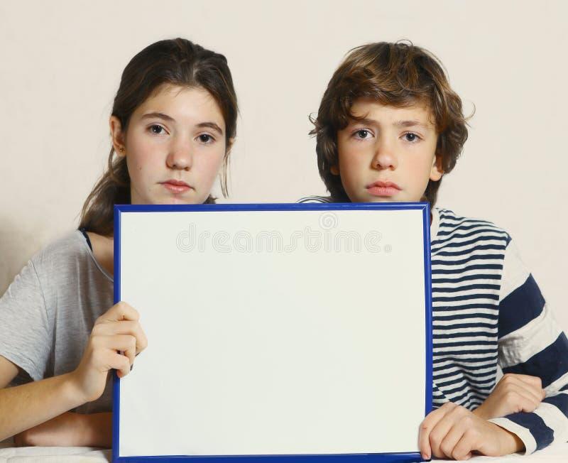 Tonåriga ungar pojke och tomt papper för flickahåll täcker royaltyfria foton