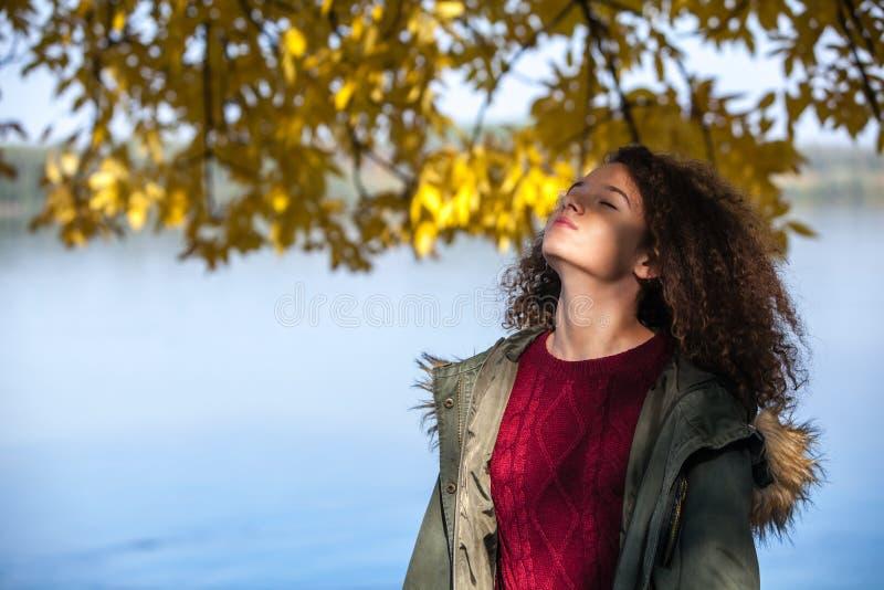 Tonårigt flickaanseende för lockigt hår vid floden fotografering för bildbyråer
